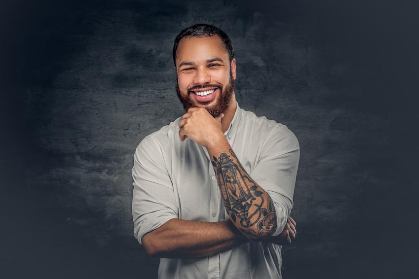 Lächelnder Mann mit tätowiertem Arm